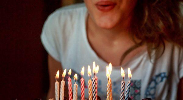 přání k narozeninám, dívka sfoukává svíčky z narozeninového dortu